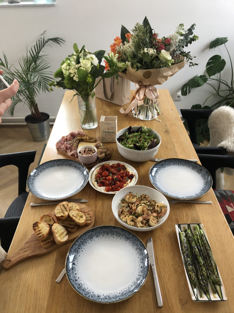 An image of a table full of breakfast dishes and flowers