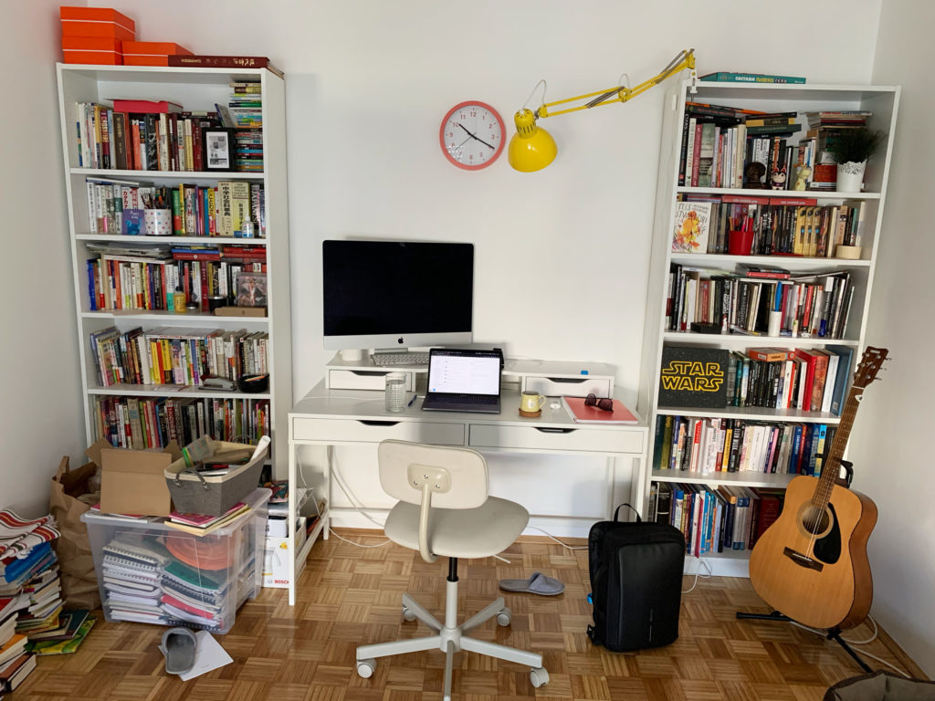An image of a FishingBooker teammate's work from home space including a computer, bookshelves, and a guitar